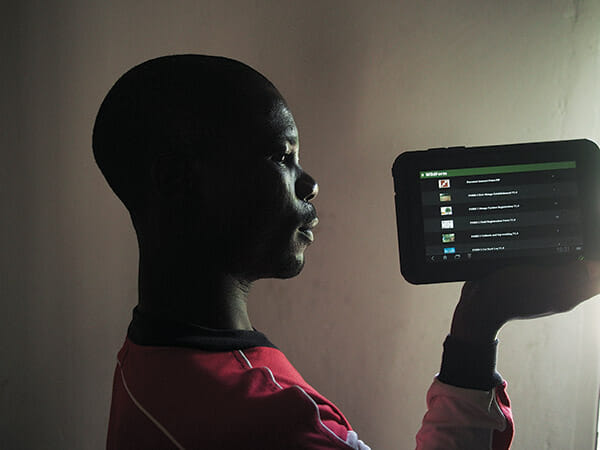 Hendrix, a Malawi Mangoes employee holds a tablet used as a registration tool for horticulturists visiting small farmers.