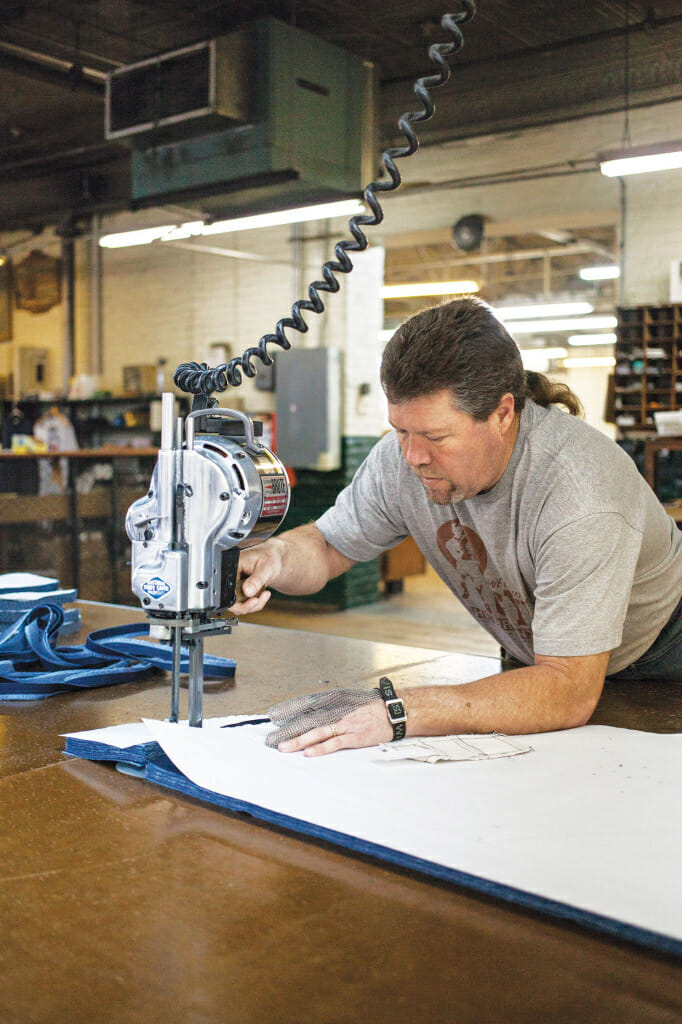 Employee Will Holt cuts fabric from a paper pattern