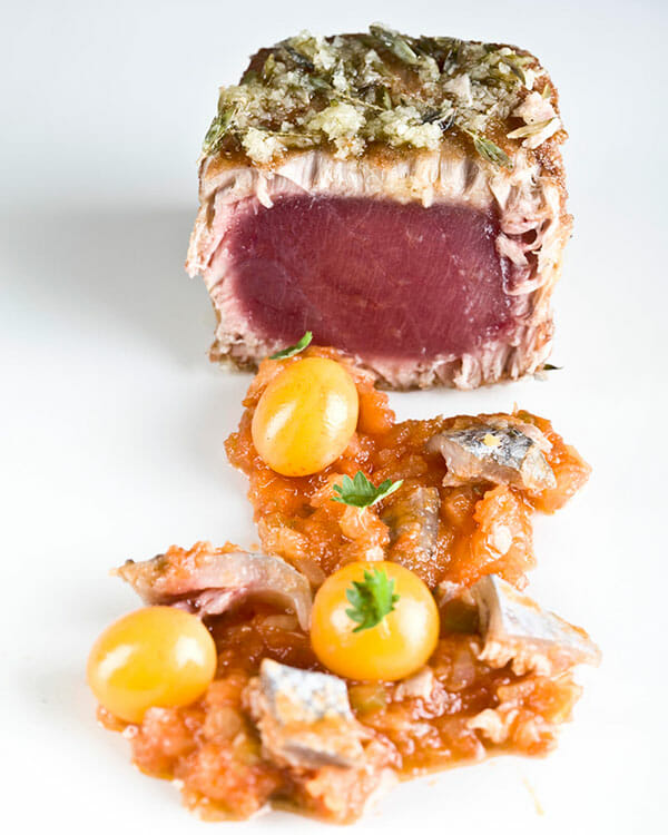 Chicharrón de atún, sobre una fritada de tomates y pellejito (Crackling tuna with fried tomatoes and tuna skin).