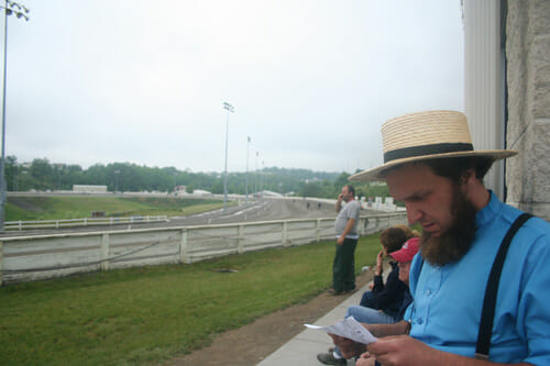 Brenneman consults the program as horses warm up for one of the day's qualifying races at The Meadows racetrack in Washington, Pa.
