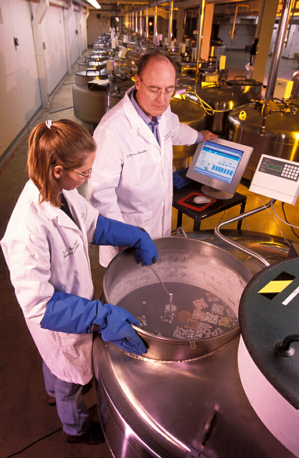 Dr. Harvey Blackburn and technician Ginny Schmit storing samples in liquid ntrogen.