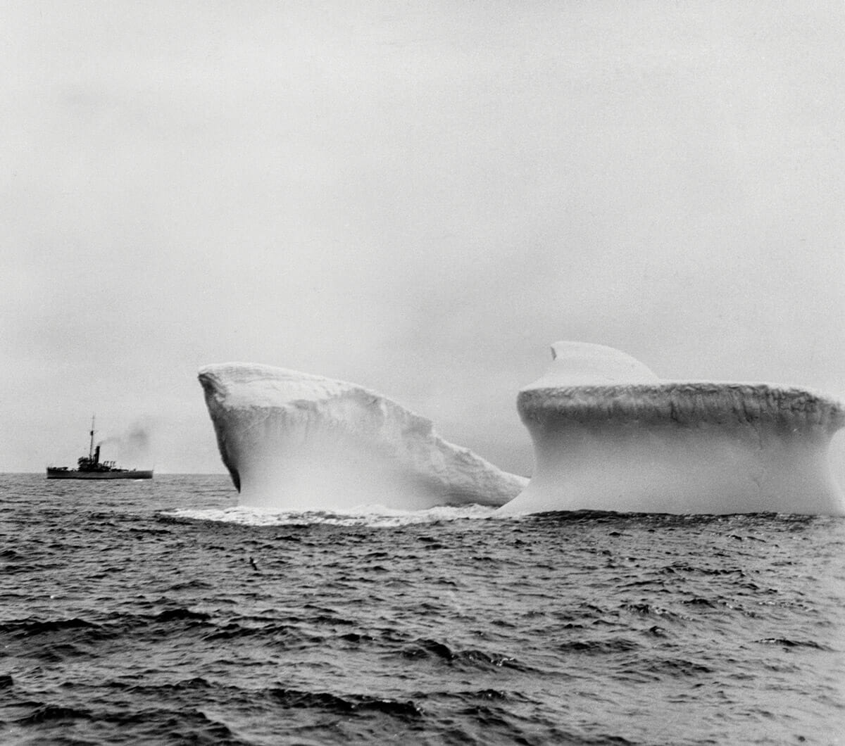 Ship sailing past iceberg in Antarctic waters.