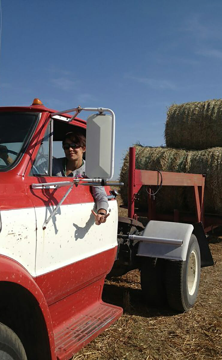 Katie collecting round bales of hay at her farm.