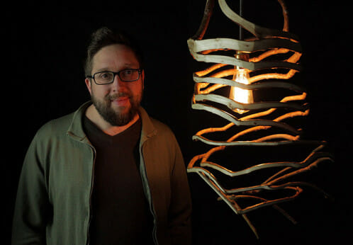 British furniture maker Gavin Munro stands with a lamp he grew.