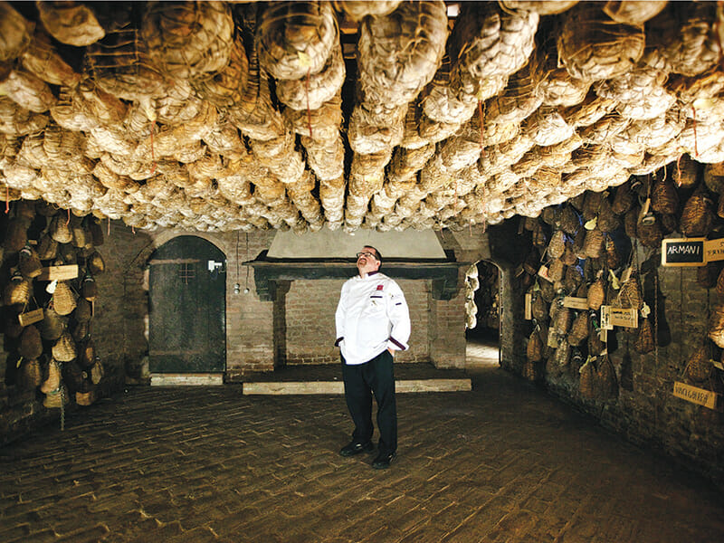 Massimo Spigaroll, chef and co-owner, stands amidst his hundreds of culatello hams hanging to dry.