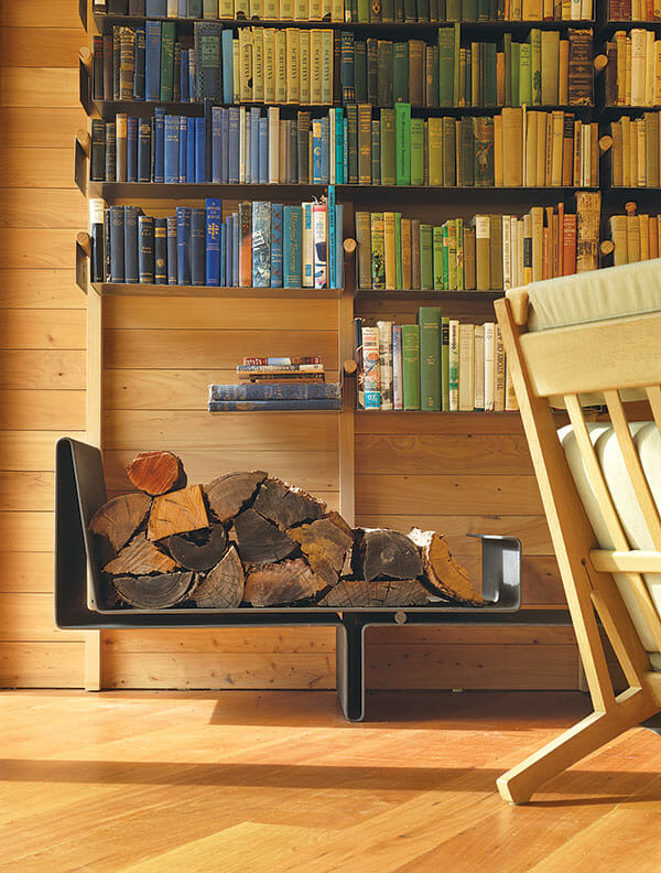 A bookshelf over a stack of firewood.