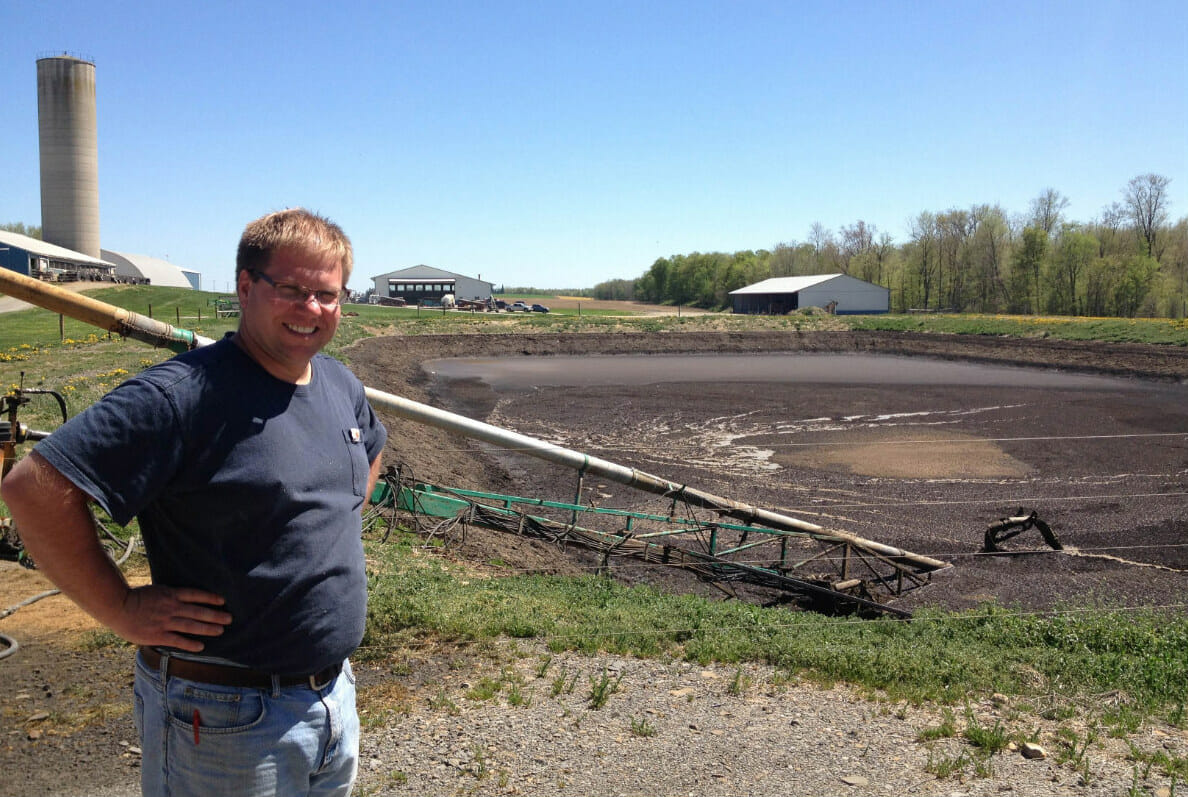 Neil Rejman, an Upstate New York dairy farmer, stands before a lagoon of manure mixed with acid whey. This slurry will be turned in to energy by a machine called an 'anaerobic digester.'