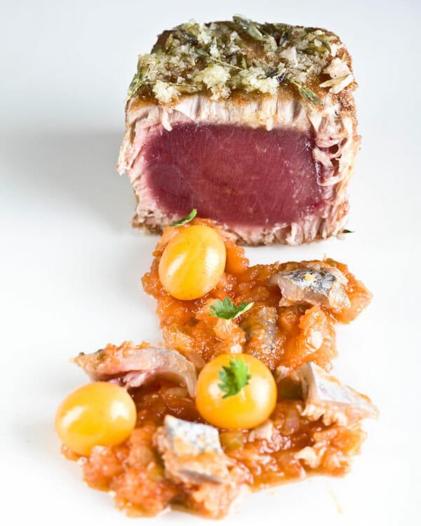 ChicharrÁ³n de atÁºn, sobre una fritada de tomates y pellejito (Crackling tuna with fried tomatoes and tuna skin).