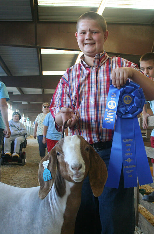 Shelvin Arey, 12, and his goat, Fuzz, celebrate a first-place finish in a heat of the mediumweight class.