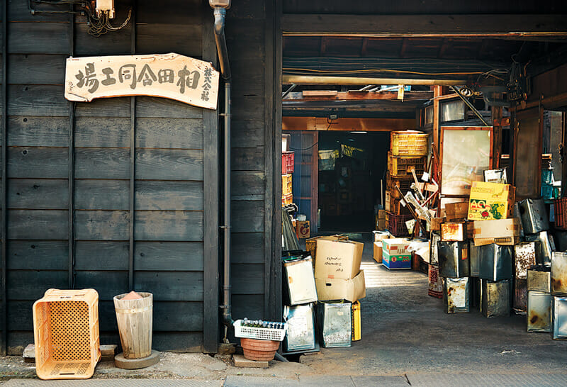 The factory's entrance. The wooden sign bears the company name, Aida Godo Kojo.