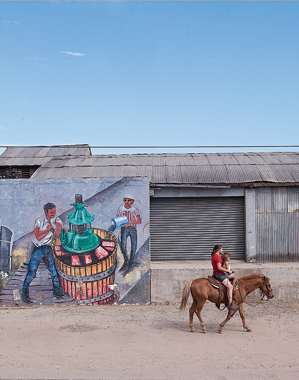 Two locals ride by La Escuelita, whose exterior is made of glass bottles, repurposed wine barrels and mattress springs.