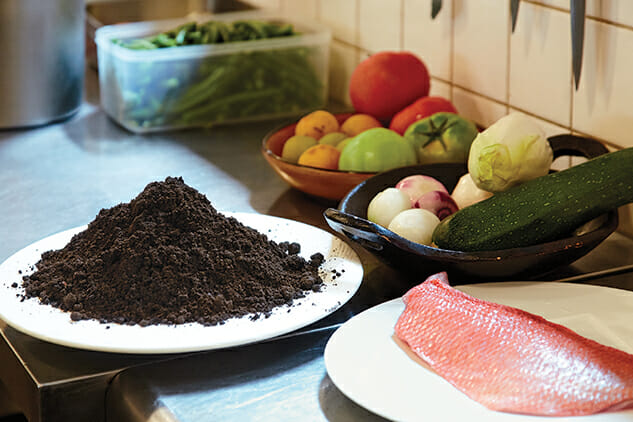 A plate of soil with fresh vegetables and sea bream (a kind of fish).