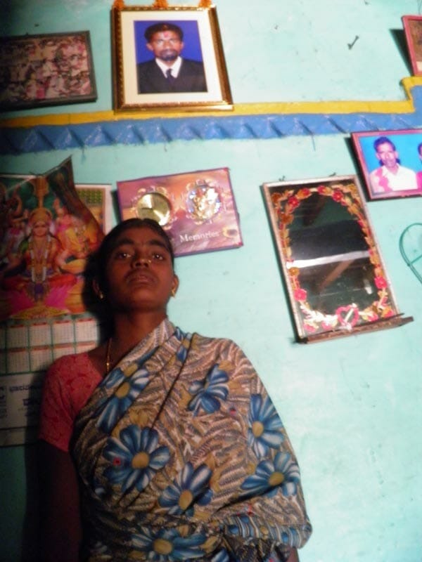 25-year-old Shanthamma, standing underneath a photo of her husband, Rama Krishna.