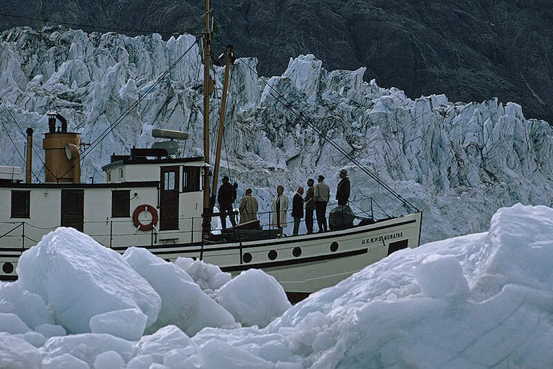 National Park Service boat travels between glacier and iceberg.