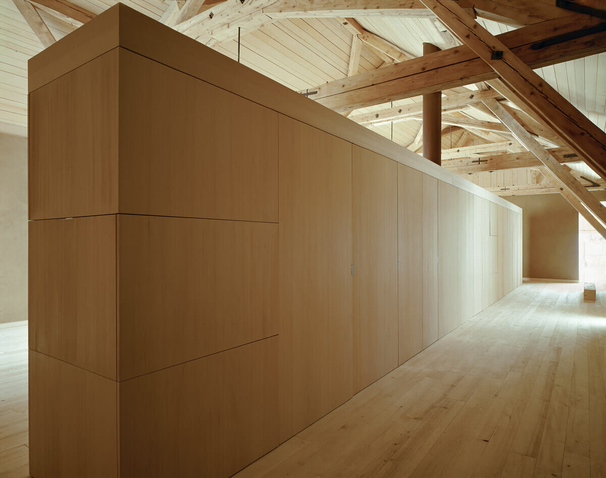 Inside the barn, long cupboards separate public space from private space.