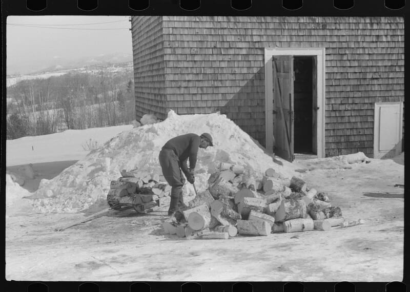Hired hand on Mr. Dickinson's farm, splitting logs for winter fuel. Lisbon, near Franconia, New Hampshire. Photographer: Marion Post Wolcott, ca. March 1939 or 1940.