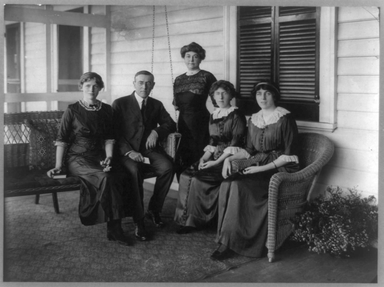 "Woodrow Wilson, seated posed on swing on porch, facing front, with his wife and three daughters."" 1912. PHOTO: Library of Congress."