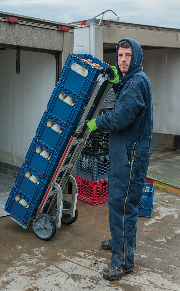 One of the farm's workers loading milk bottles onto a truck. From dawn till dusk, the milk production and the shipping and receiving operations are working in parallel.