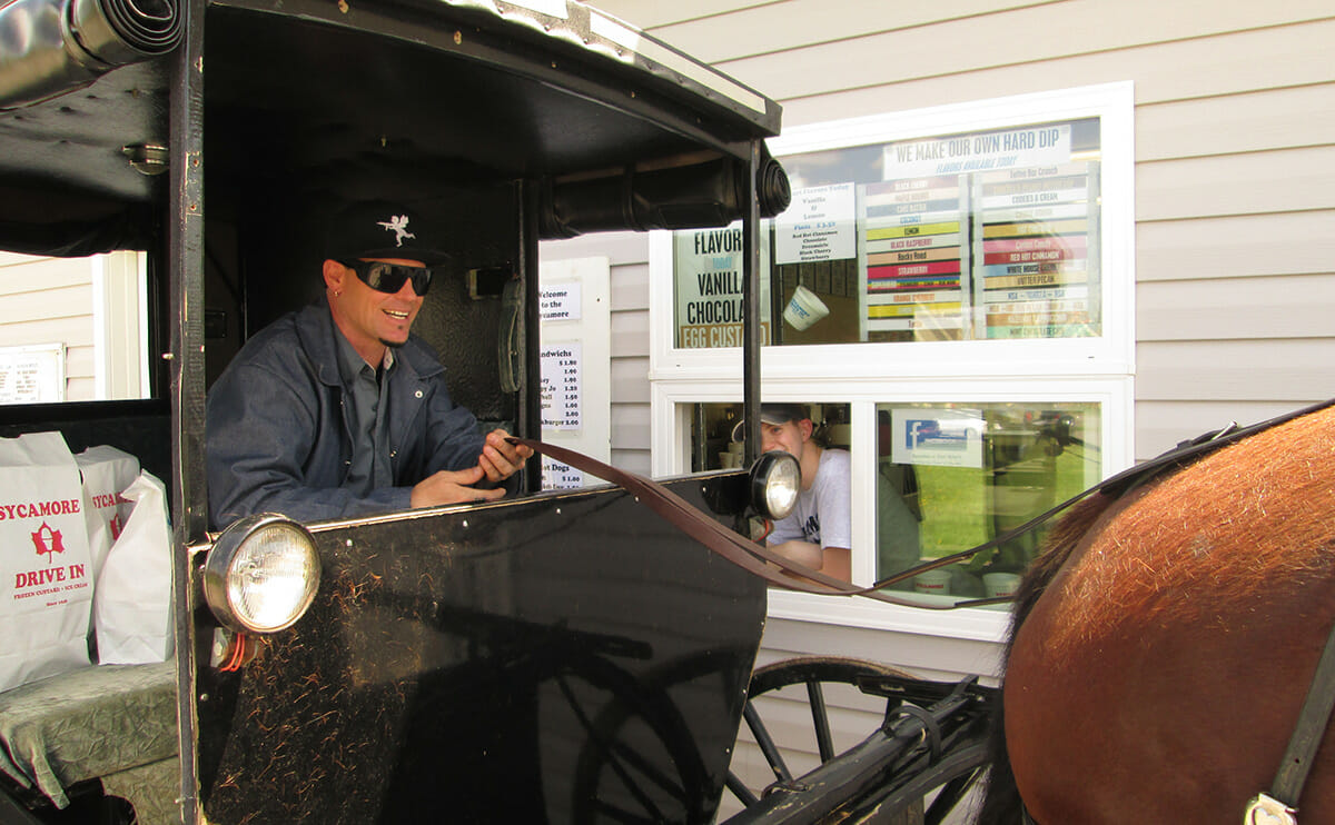 Vanilla Ice steering a horse and buggy through a drive through.