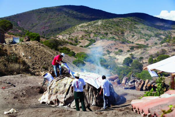 Workers cover the roasting pit.