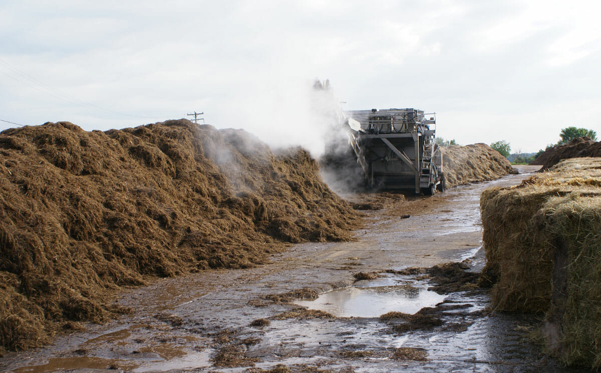 Machines turn rotting hay to make compost.