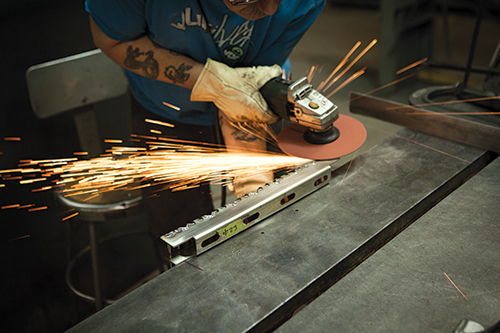 A welder grinds the back edge of a V-channel surface flush.