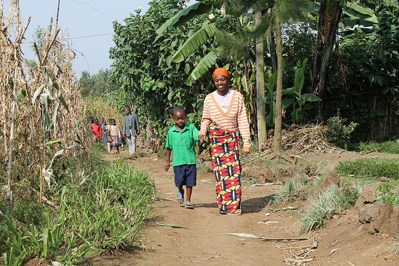 A Rwanda mother walks her children to preschool.