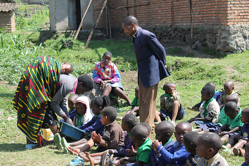 Pastor Donat Hatangimana and his wife (with the baby sleeping on her back) as the children wash their hands before eating the eggs. Hygiene is an important lesson at the preschool.