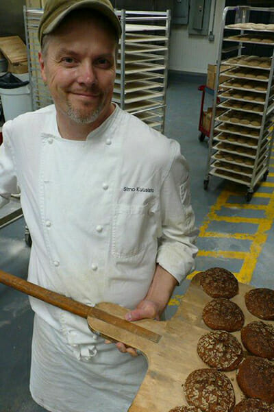 Kuusisto removes warm rye bread from the oven in his Brooklyn shop, Nordic Breads. / Courtesy Nordic Breads.