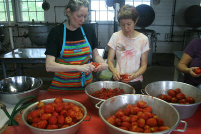"""Fonda Nichols (left) and Lise Metzger, friends from Falls Church, Va., drove two hours to can 75 pounds of tomatoes at the Keezletown Community Cannery """""""" one of the last remaining public canneries opened during the World War II Victory Garden era."""