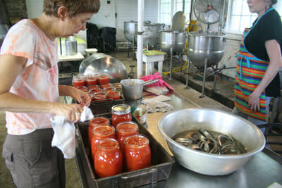 Lise Metzger wipes the rims before putting lids on the jars.