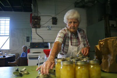 Vera Bowman, who has been using the cannery in Keezletown for decades, puts lids on her jars of zucchini pickles.