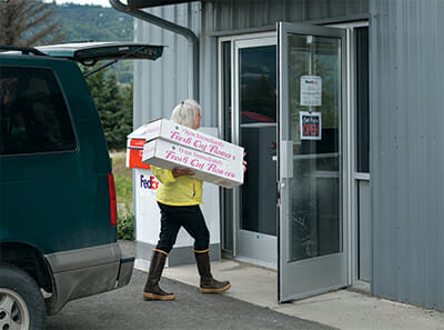 Beth VanSandt takes her daily flower shipment to the local FedEx facility near Homer Airport.