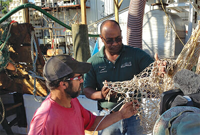 Thornell King repairs nets with one of his crew.
