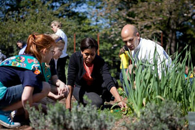 Sam Kass and Michelle Obama plant on the South Grounds with Girl Scout Troop 60325. / Courtesy the White House.