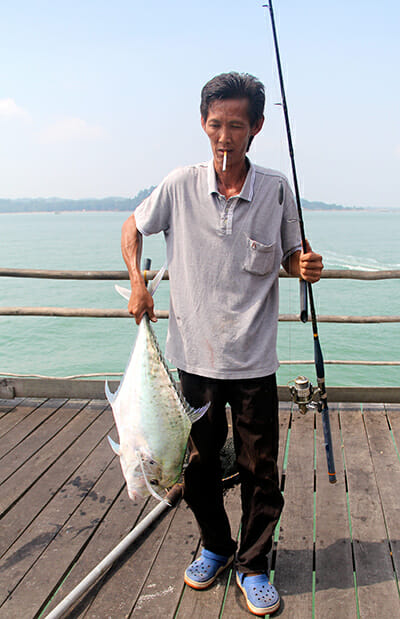 A fisherman poses with the catch of the day - a diamond trevally. Testament to declining fish populations, this was the first major catch of the weekend.