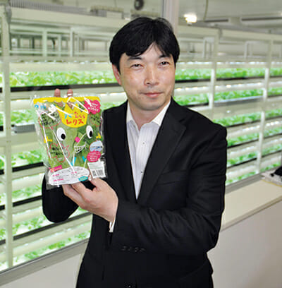 President Shigeharu Shimamura of Mirai Co. holds a bag of lettuce produced at a large-scale plant factory in Kashiwa. / Courtesy GE Lighting.