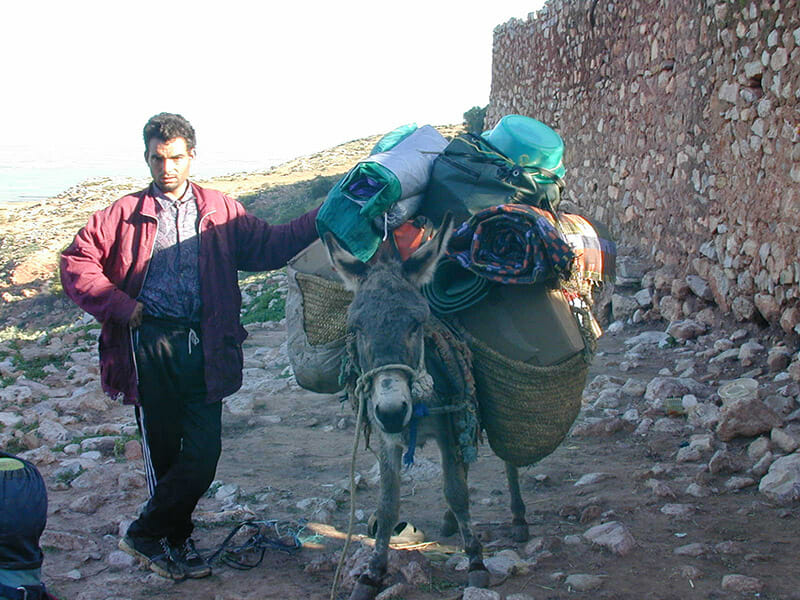 A man stands with a loaded donkey. Flickr/goatchurchprime.