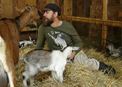 A goat kisses Michael Stanitis. / Courtesy Julie Buckles.